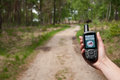 Finding a route woman hand hold gps device to secure the through the forest Royalty Free Stock Images
