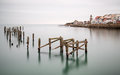Fine art landscape image of derelict pier in milky long exposure decayed Stock Photos