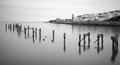 Fine art landscape image of derelict pier in milky long exposure decayed Stock Photo