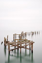 Fine art landscape image of derelict pier in milky long exposure decayed Royalty Free Stock Photo