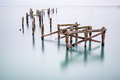 Fine art landscape image of derelict pier in milky long exposure decayed Royalty Free Stock Photography