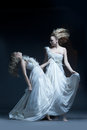 Fine art photo of a dancing beautiful young girl in white wedding dress with multiexposition Stock Image