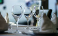 Fine restaurant dinner table setting by wineglass and napkin Royalty Free Stock Images