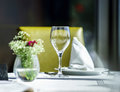 Fine restaurant dinner table setting by wineglass and napkin Stock Photos
