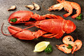 Fine selection of crustacean for dinner lobster and shrimps on dark stone plate food background Royalty Free Stock Photos