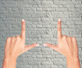 Finger frame over grey brick wall Royalty Free Stock Photo