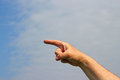 Finger pointing to the left a with a blue sky and cloudy background Royalty Free Stock Photo
