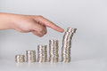 Finger pushing a pile of coins, column of coins falls , business Royalty Free Stock Photo