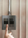 A finger is turning on a grey or black metallic light switch
