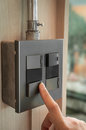 Finger is turning on a grey or black metallic light switch