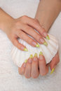 Fingernails and seashell girls green spotty on a white towel with big in her hand Royalty Free Stock Photos