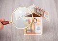 Fingers holding magnifying glass to analyze euro house Royalty Free Stock Photo