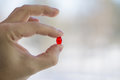 In fingers are holding a red pill. Blurred light background Royalty Free Stock Photo