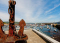 Finisterre harbour galicia spain with an ancient ship s anchor and fishing boats in the background Stock Image