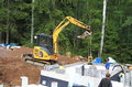 Finland an excavator lowering a compactor mini digger lowers into the foundation of sauna Royalty Free Stock Photos