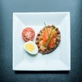 Finnish breakfast traditional karelian pasty topped with the piece of cold smoked salmon seasoned with chives tomato and egg are Royalty Free Stock Image