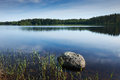 Finnish lake with trees in the background and a big rock in the foreground Royalty Free Stock Photos