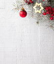 Fir branch with Christmas decorations on the white wooden plank. Royalty Free Stock Photo