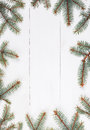 Fir branches in form of frame on white wooden table. Christmas and Happy New Year composition.Flat lay, top Royalty Free Stock Photo