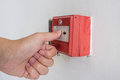 Fire alarm closeup shot of human hand pushing system Stock Photo