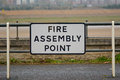 Fire assembly point sign in car park outside building Royalty Free Stock Image