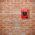 Fire break glass alarm switch on brick wall background Royalty Free Stock Photo