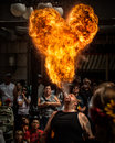 Fire breather street performer and ball of flame a blows out a huge from his mouth in front audience Stock Photography