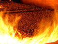 Fire the combustion of biomass in the form of pellets in the boi boiler stoker coal visible through open hatch you can see Stock Photos