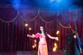 Fire dancer twirling flaming batons on stage exotic dark haired female wearing bright pink and orange costume two baton apparatus Royalty Free Stock Photo
