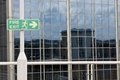 Fire exit sign with modern glass building behind Royalty Free Stock Photography