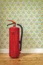 Fire extinguisher in front of retro flower wallpaper Royalty Free Stock Photo