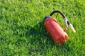 Fire extinguisher laying on green grass red Royalty Free Stock Photos
