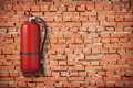 Fire extinguisher on red brick wall Stock Photo