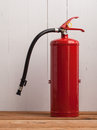 Fire extinguisher on wood floor Royalty Free Stock Photo