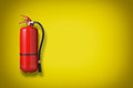 Fire extinguisher on the yellow wall Royalty Free Stock Images