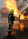 Fire fighter fighting large fire fuel tank Royalty Free Stock Images