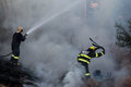 Fire fighters from the city of johannesburg busy putting out a one fighter is using water hose to douse Stock Photo