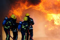 Fire fighters fighting large fire with hose Royalty Free Stock Image