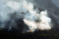 Fire fighting helicopter dropping water on a on a mountain late afternoon Stock Image