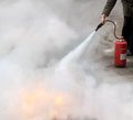 Fire fighting a woman demonstrating how to use a extinguisher Royalty Free Stock Photos