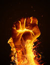 Fire fist hand consumed in flames on black background Royalty Free Stock Images