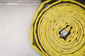 Fire hose coiled yellow with a chrome pattern Royalty Free Stock Photo