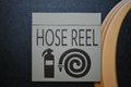 Fire hose point a sign showing the nearest reel location Royalty Free Stock Photos