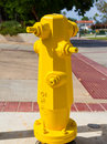 Fire hydrant freshly painted yellow Stock Photo