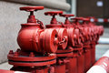 Fire hydrant a row of red outside commercial building Stock Photo