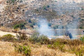 Fire in a palestinian field by wall of separation bil palestine may th person wearing gas mask trying to put out caused gas mask Royalty Free Stock Photos
