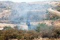 Fire in a palestinian field by wall of separation bil palestine may th person wearing gas mask trying to put out caused gas mask Stock Photography