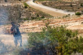 Fire in a palestinian field by wall of separation bil palestine may th person wearing gas mask trying to put out caused gas mask Stock Photos