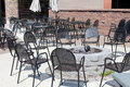 Fire pit and black metal chairs surrounding it restaurant tables in a courtyard with stone for guests to gather around after a Stock Photos