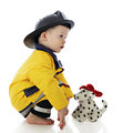 Fire pup faces baby fireman profile of a squatting in front of his toy dog on a white background Royalty Free Stock Photos